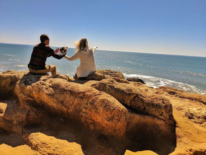 Couple on sandstone boulders at ocean whale watching woman pointing out to sea.