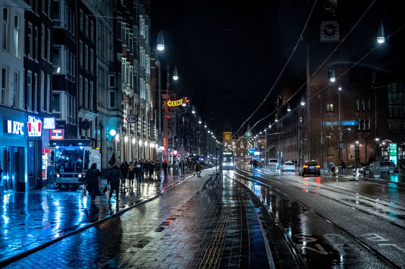 City Night Illuminated Architecture Building Exterior Street Transportation Built Structure Wet Road Rain Street Light City Street City Life Car Motor Vehicle Mode Of Transportation Incidental People Land Vehicle Outdoors Track Light Rainy Season Nightlife