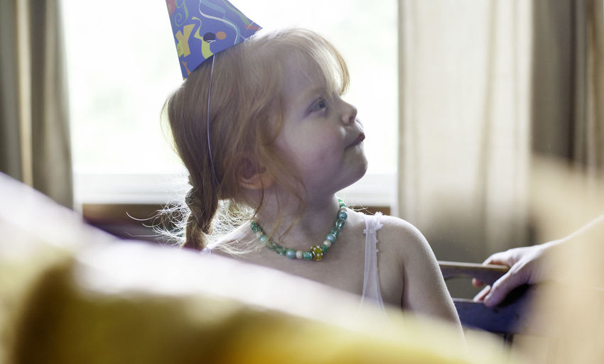 Close-up of girl wearing party hat at home