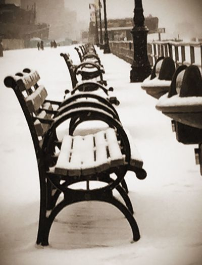 Snow covered chairs and table on street during winter
