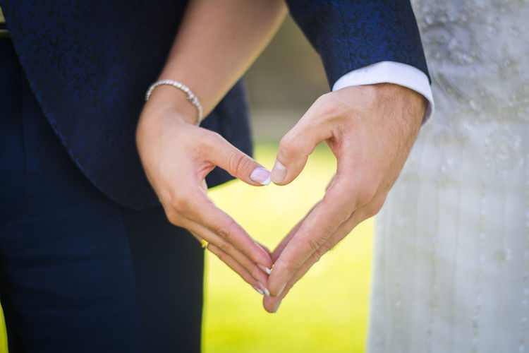 Midsection of couple holding heart shape