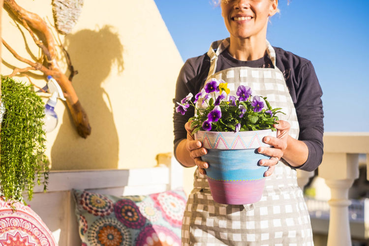 woman at work with plants in the terrace at home Aprons Beauty In Nature Casual Clothing Day Flower Fragility Freshness Front View Growth Holding Lifestyles Nature One Person Outdoors People Portrait Sky Smiling Standing Sunlight Terraced Field Women Young Adult Young Women