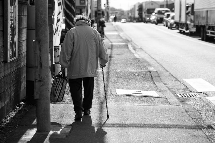 Rear View Of Senior Woman Walking On Sidewalk