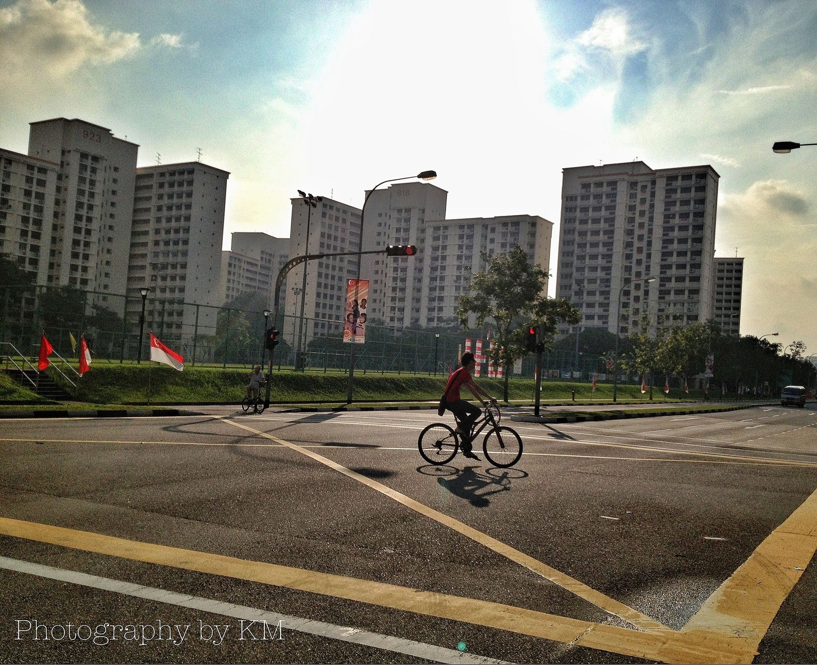 transportation, land vehicle, mode of transport, building exterior, architecture, bicycle, built structure, city, street, sky, road, car, cloud - sky, road marking, stationary, city life, parking, parked, riding