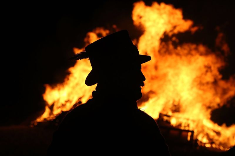 Close-up of silhouette man against bonfire