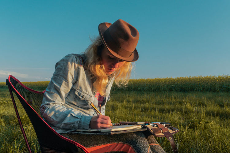 Woman Drawing In Book While Sitting On Field Against Clear Sky
