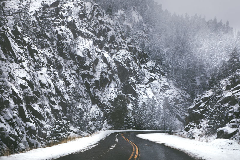Transportation Road Cold Temperature Winter Snow No People Day Nature Motion Direction Beauty In Nature The Way Forward Scenics - Nature Mountain Sign Curve Outdoors Non-urban Scene Water Snowing Crash Barrier