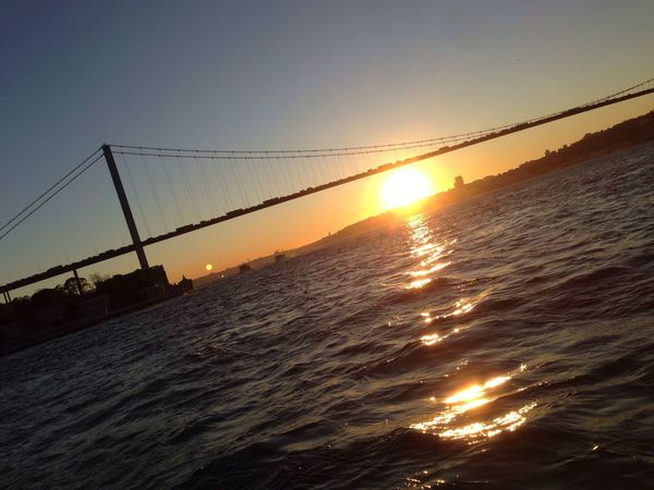 Sunset Sea Sun Water Sky Nature Sunlight Outdoors No People Scenics Suspension Bridge Silhouette Architecture Clear Sky Wave Horizon Over Water Vapor Trail Day