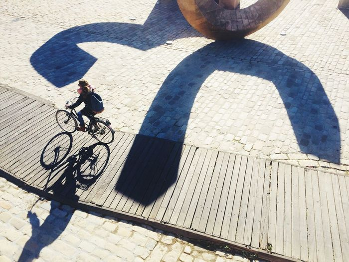 High angle view of woman cycling on boardwalk during sunny day