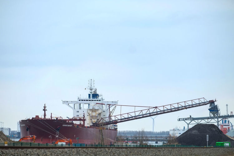 Doel, Antwerp, Belgium – February 2019: Large cargo ship unloading in the dock of the Antwerp harbor Sky Architecture Built Structure Nature Industry Ship No People Day Building Exterior Factory Nautical Vessel Business Freight Transportation Transportation Machinery Copy Space Commercial Dock Water Outdoors Shipping  Industrial Equipment Industrial District