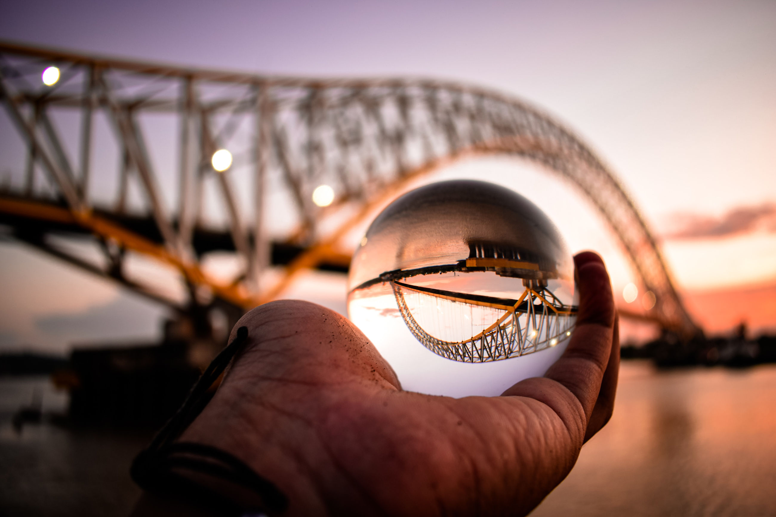 focus on foreground, sky, one person, water, human hand, holding, hand, close-up, real people, human body part, nature, lifestyles, sunset, selective focus, unrecognizable person, clear sky, body part, personal perspective, outdoors, finger