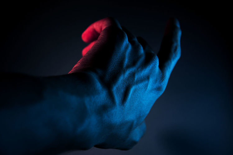 Male hand illuminated with blue light