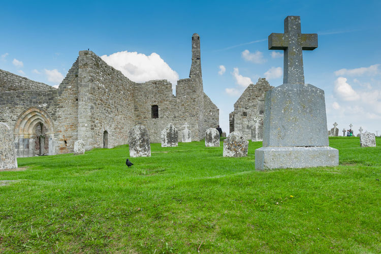 Clonmacnoise monastery ruin Historic History Clonmacnoise Monastery Ruins Ruins Architecture Cross Spirituality Religion Sky Grass Architecture Green Color Cloud - Sky Tombstone Grave Death Mourning Crucifix Grief The End Cemetery Graveyard Place Of Burial Gravestone Memorial Tomb Historic Cross Shape