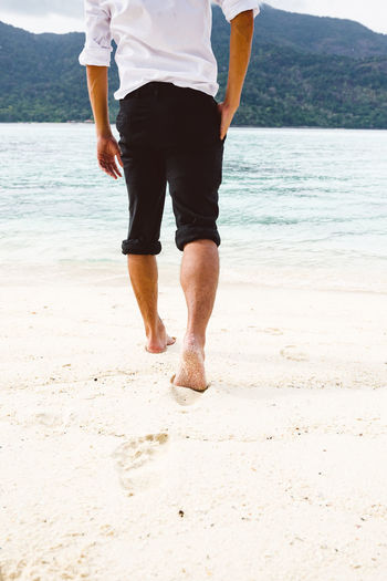 Low section of man walking on shore at beach