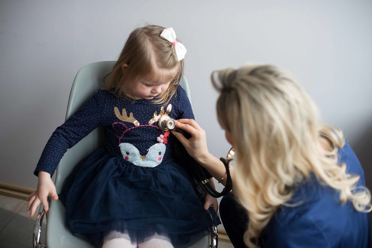 Pediatrician examining cute girl in medical clinic