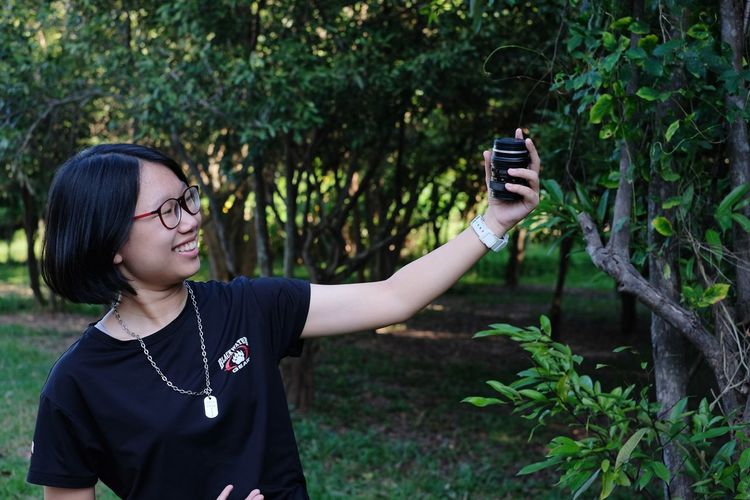 Girl holding camera lens in forest