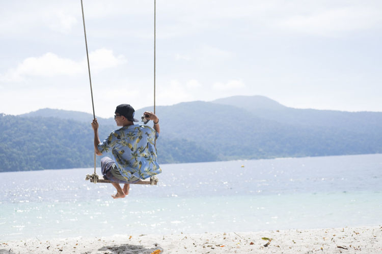Rear view of mid adult man swinging at beach against sky