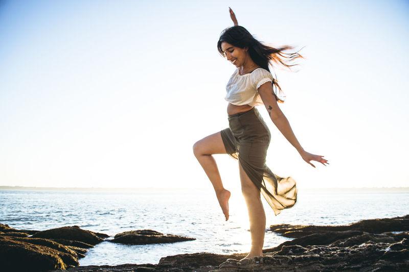 Full length of woman on beach against clear sky