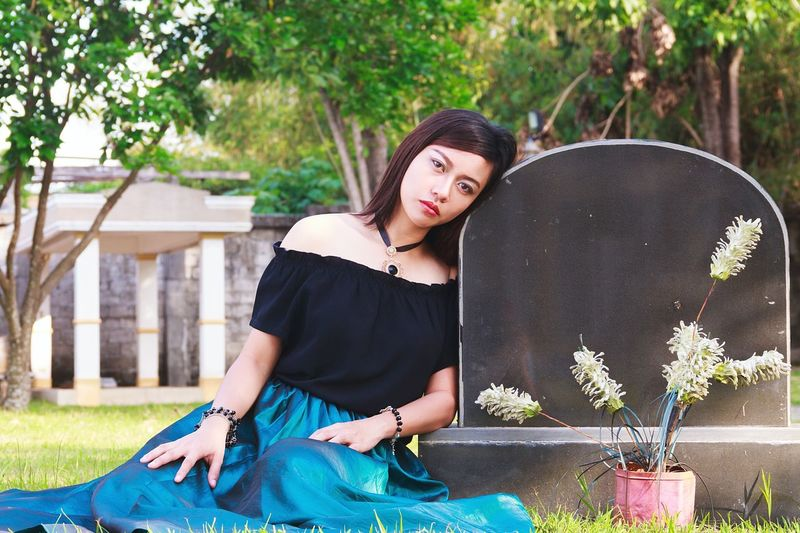Portrait of sad woman leaning on tombstone in cemetery