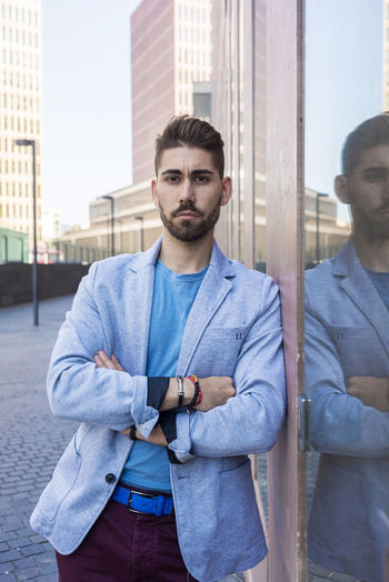 Portrait of handsome man with arms crossed standing by wall in city