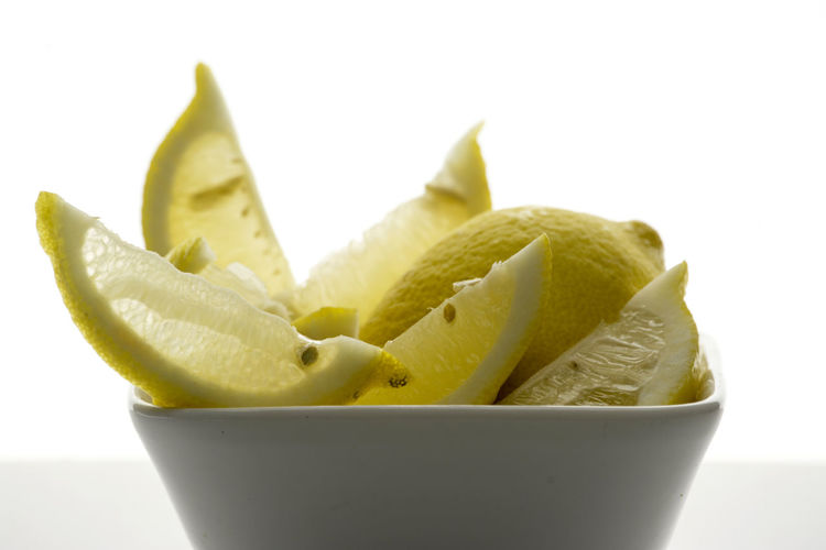 Close-up of lemon slices in bowl on table against white background