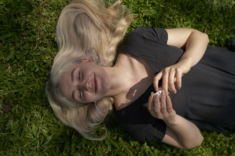 Young woman lying down on field