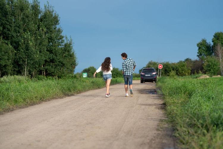 Rear view of women walking on road against trees