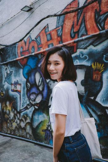 Portrait of teenage girl standing against graffiti wall