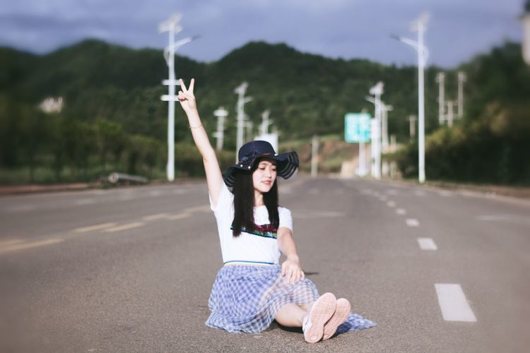 Full Length Of Woman Gesturing Peace Sign While Sitting On Road