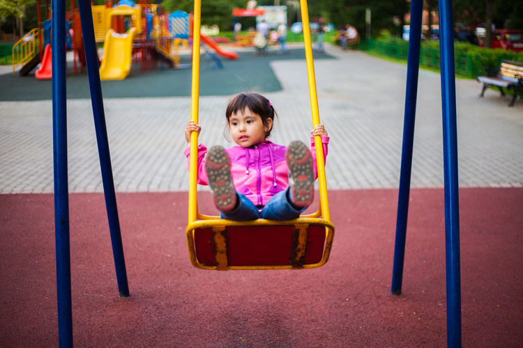 Boy sitting on swing at park