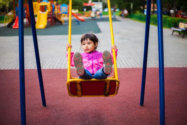 Cute girl swinging on swing in playground
