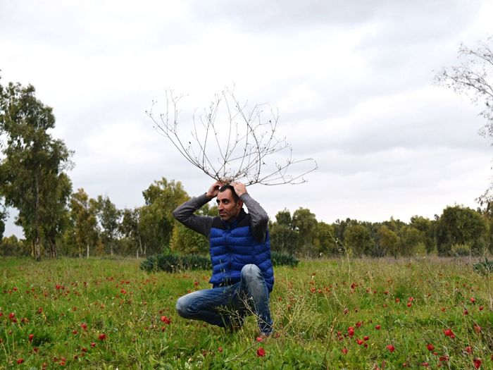 Man Holding Branch While Crouching On Poppy Field
