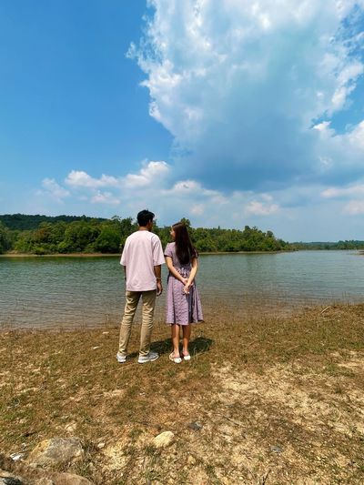Rear view of couple walking on lake against sky