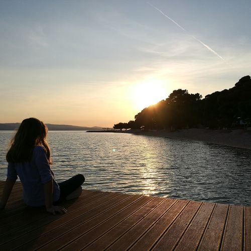 Rear view of woman sitting on pier at lake during sunset