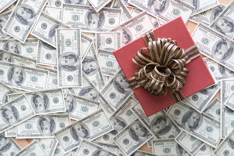 High angle view of gift box with paper currencies on table