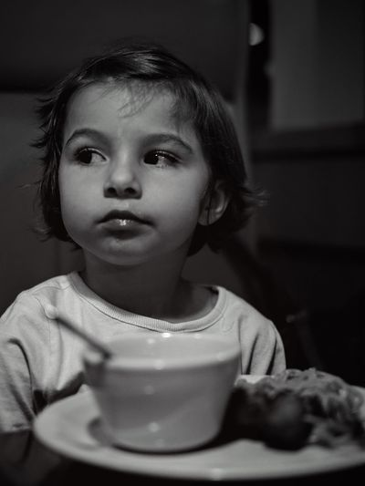 Close-up of girl looking away while food in plate on table