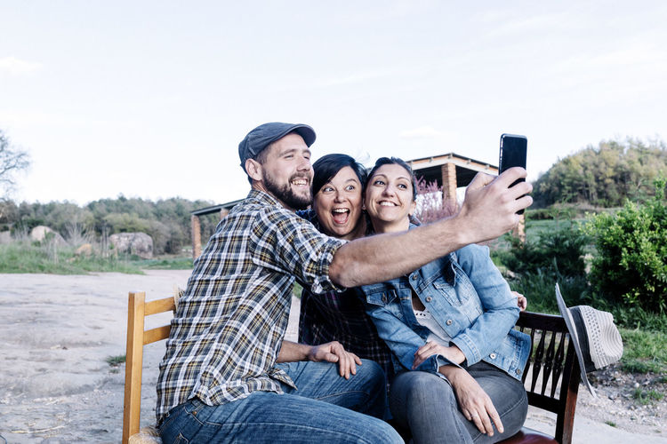 Happy friends taking selfie in rural area against clear sky