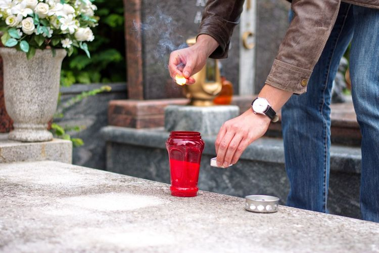 Midsection of man lighting candle in cemetery