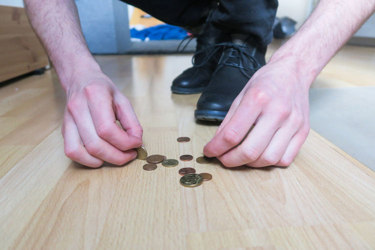 Two male Hands picking up euro coins from wooden floor Human Hand Coin Finding New Frontiers Find Your Park Money Business Investment Finger