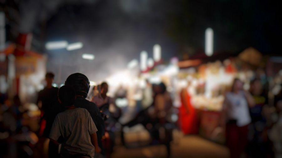 Crowd on illuminated street in city at night