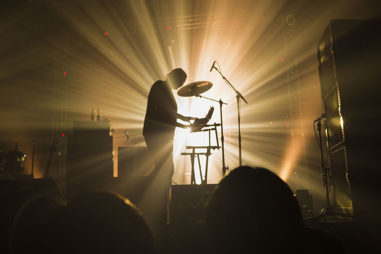 Silhouette man playing piano at music concert