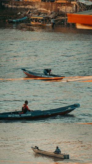 People rowing boat in water