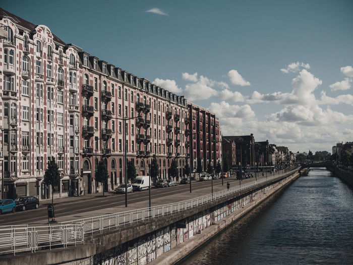 Bridge over canal by buildings against sky