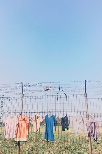 clothe EyeEmNewHere TheWeekOnEyeEM EyeEm Selects The Still Life Photographer - 2018 EyeEm Awards The Creative - 2018 EyeEm Awards Hanging Consumerism Clothing Multi Colored Sky Grass Clothesline Hooded Beach Chair Coat Hook Clothes Rack Dryer  Drying Clothes Clothespin Wooden Post Cloth