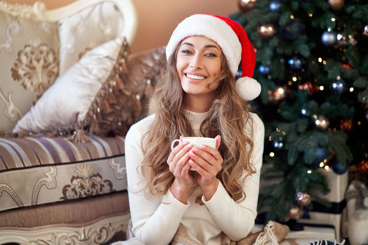 Happy young woman with hat on christmas tree