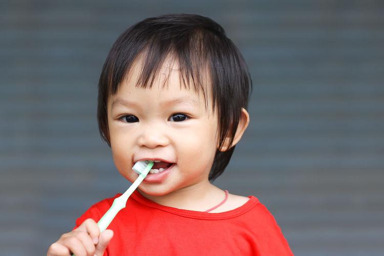 Portrait of cute baby girl brushing teeth