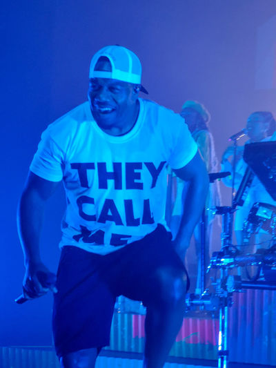 rudimental Text Baseball Cap Musicevent Musicperformance music brings us together Music Industry Rudimental  One Man In The Foreground Dancing And Singing Portrait Men Standing City Occupation Blue Communication