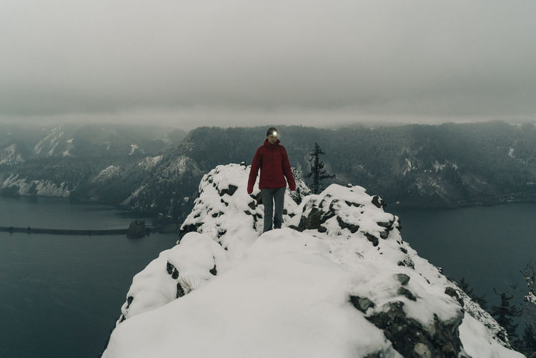 Man standing on mountain against sky during winter