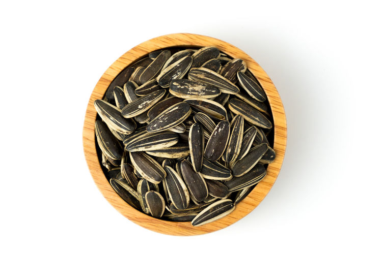 Close up of sunflower seeds isolated in wooden bowl against top view on white background and clipping path. Sunflower Seeds White Background Isolated Food Organic Agriculture Snack Ingredient Shell Pile Healthy Diet Tasty Nutrition Dry Roasted Close-up Objects Vegetarian Heap Clipping Path Cereal Bowl Wooden