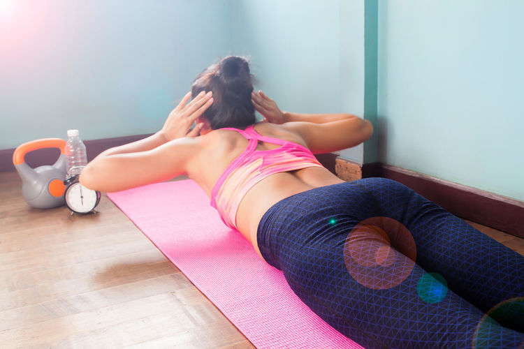 Rear view of woman exercising on exercise mat at home